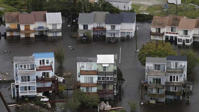 In this Sept. 16, 2018 photo, homes along the New River are flooded as a result of high tides and rain from hurricane Florence, which moved through the area in Jacksonville, N.C.