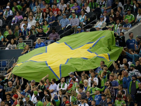 Sounders supporters pass around a giant star, the symbol