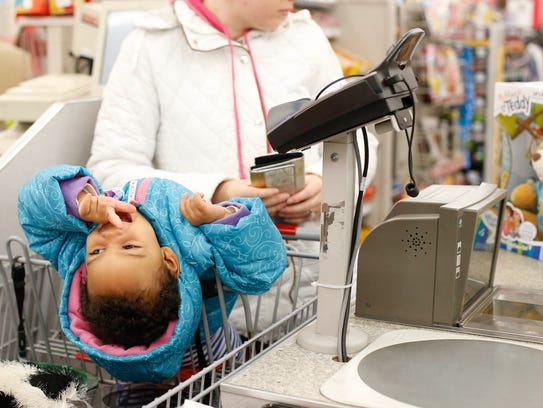Amadika Hamednur, 2, of Des Moines, waits in the cart as family members ring up their purchases at the Kmart in Urbandale on Black Friday in 2016.