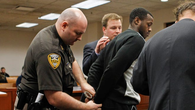 Former University of Louisville basketball player Chris Jones is handcuffed after being ordered under home incarceration after he plead not guilty to rape and sodomy charges.