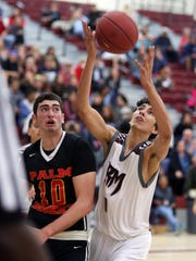 Rancho Mirage's Matt Barajas-Tiedeman grabs a rebound while Palm Desert's Alex Mcgrath looks on during the game in Rancho Mirage on Saturday.