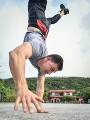In this file photo, Justin Kohn performs a walking handstand at CrossFit Gof Metgot.