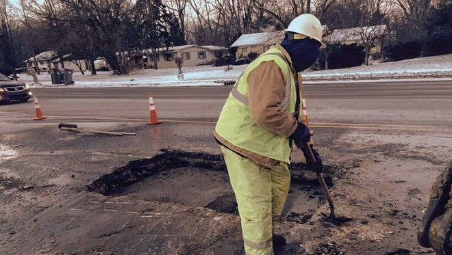 A Citizens Energy workers helps finish repairs to a broken water main at Madison and Edgewood.