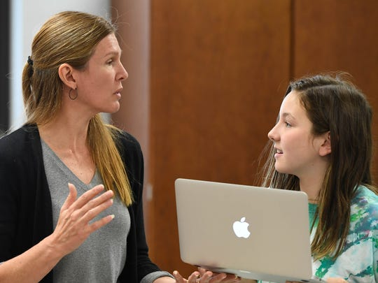 Julie Kissenger, a sixth grade teacher at Mount Vernon Junior High, answers questions from Olivia Culley about a class project in their language arts class.