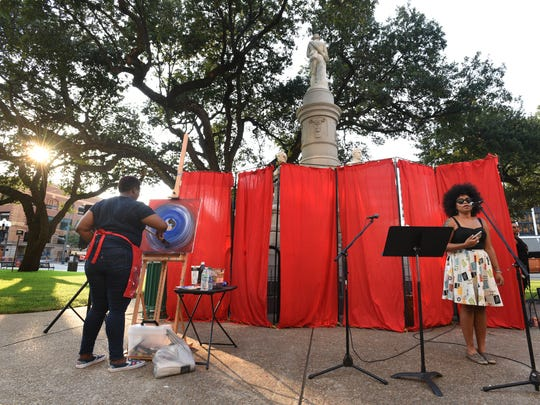 Whitney Tatec paints at Lest We Forget: A Community Performance Art Event held in front of the downtown Confederate monument.