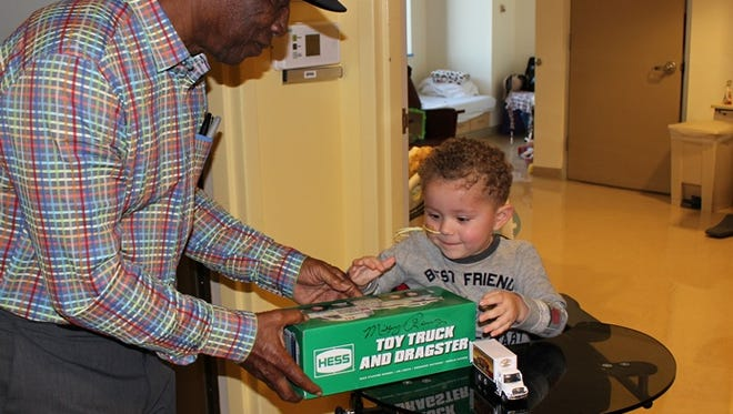Former New York Yankees player, Mickey Rivers, gives a 2016 Hess Truck to a young Children's Specialized Hospital patient.