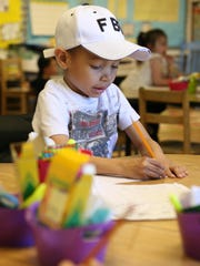 As a kindergartner at Lincoln Elementary Trayson Harrell works on writing a sentence.