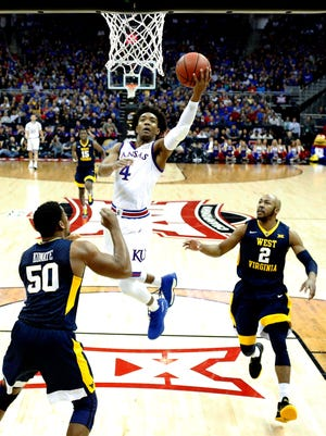 Devonte' Graham of the Kansas Jayhawks drives toward the basket as Sagaba Konate and Jevon Carter of the West Virginia Mountaineers defend during the Big 12 Basketball Tournament Championship game at Sprint Center on March 10.