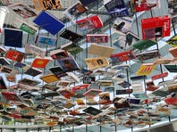 "English sculptor Richard Wentworth's largest site-specific installation in North America, ""False Ceiling--Indianapolis,"" has taken two weeks to install in the Efroymson Family Entrance Pavilion at the Indianapolis Museum of Art. The final stage of the installation, which consists of books collected during a public book drive in Indianapolis this summer, is shown on Tuesday, September 22, 2015. The London artist will have a free public conversation in The Toby at the IMA at 6 p.m. Thursday with the IMA's curator of contemporary art, Tricia Y. Paik, with the official premier on Friday. Hundreds of books are strung by wire from a grid that hangs in the pavilion, giving two unique viewpoints -- from the first floor looking up at the books hanging overhead, and from the second floor looking down. After seeing the artist's same-concept permanent installation in Istanbul, Paik arranged for Wentworth to create this show for the IMA through June 5, 2016. Wentworth, 68, is known for transforming familiar matter into visual poetry."
