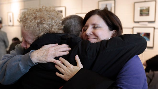 Susan Horowitz, left, and Judy Valenti, right, hug a friend in Ferndale, Mich., on March 21, 2014., after a federal judge struck down Michigan's ban on gay marriage.