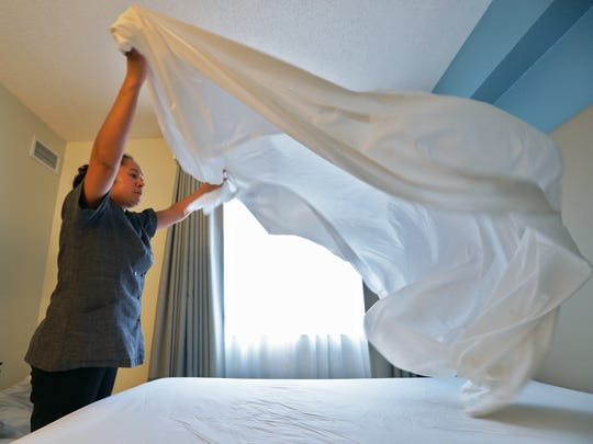 Lorena Villagomez, of Fort Myers, an employee at Homewood Suites by Hilton in Bonita Springs, prepares one of the rooms in December.