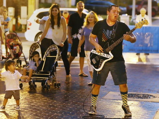 Ross Clark of the band, Rutland, performs in the rain Friday at Music Walk in downtown Fort Myers.