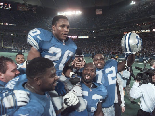 Detroit Lions running back Barry Sanders is carried on the shoulders of teammates after reaching the 2,000-yard milestone in 1997.