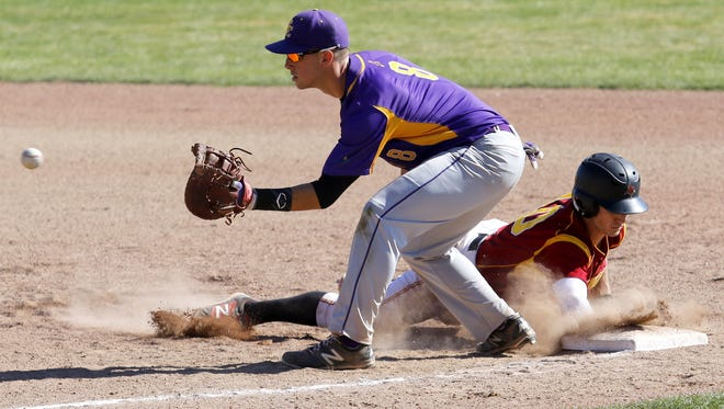 St. John Fisher's Joe Simmons dives back to the bag safely as Elmira first baseman Dylan Bellinger awaits the throw during an Empire 8 game at Dunn Field on March 26.