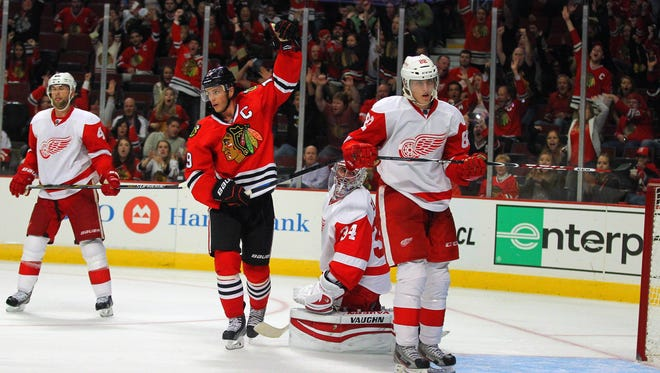 Chicago Blackhawks center Jonathan Toews (19) celebrates the winning goal scored by defenseman Duncan Keith (not pictured) with Detroit Red Wings goalie Petr Mrazek (34) reacting during the overtime period at the United Center. Chicago won 2-1 in overtime.