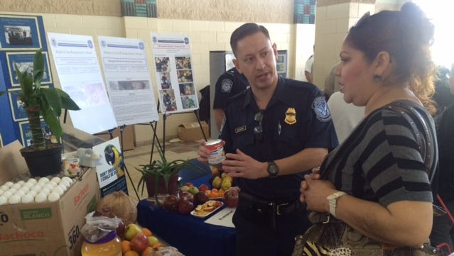 U.S. Customs and Border Protection agricultural specialist Jonathan Nogueira explains to Juarez resident Margarita Gómez which products are banned from being imported into the United States.