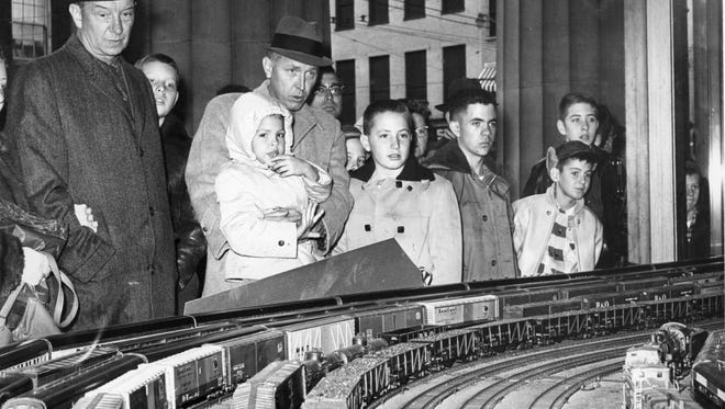 Folks watch the holiday trains in the lobby of the Cincinnati Gas & Electric Co. in December 1960.