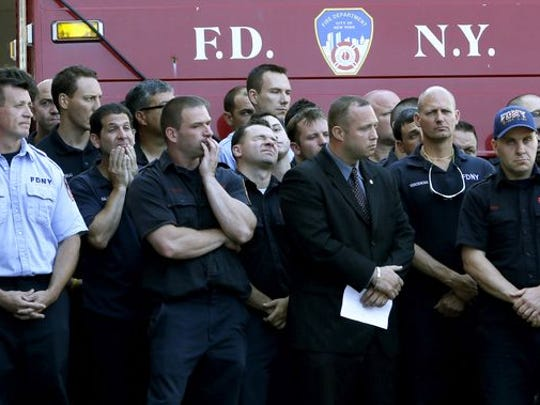 Firefighters solemnly watch as other firefighters hang bunting over the firehouse in honor of Lt. Gordon Ambelas in New York, Sunday, July 6, 2014. The Fire Department of New York is mourning the death of Ambelas, who became trapped while looking for victims in a public-housing high-rise blaze, the first to die in the line of duty in more than two years. Ambelas died Saturday after suffering multiple injuries while on the 19th floor of the 21-story building in the Williamsburg section of Brooklyn, officials said.