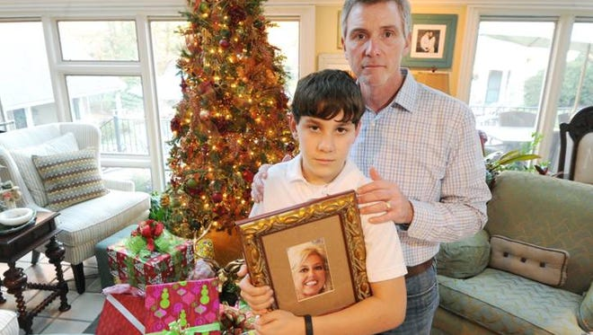 Keith Mallett, right, promised his wife before she died in September that he would raise his stepson as his own. Jack, 12, holding a photo of his mom, also lost a brother in December 2011 and his father in 2006.