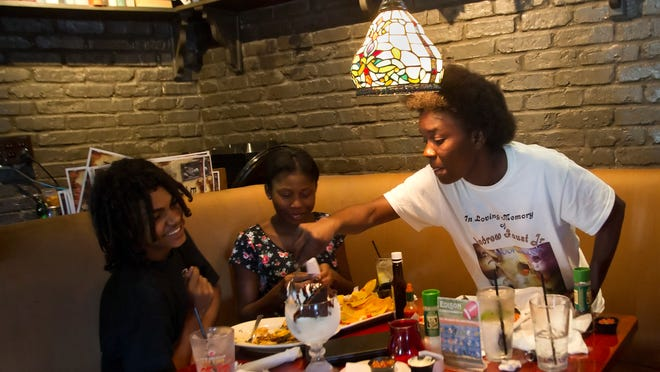 Derick Simpson,  Anika Williams,  and Toyetta Simpson, mother of Andrew Faust Jr. and Derick, celebrate Derick's 16th birthday with lunch and a chocolate brownie sundae Wednesday at the Edison Restaurant.