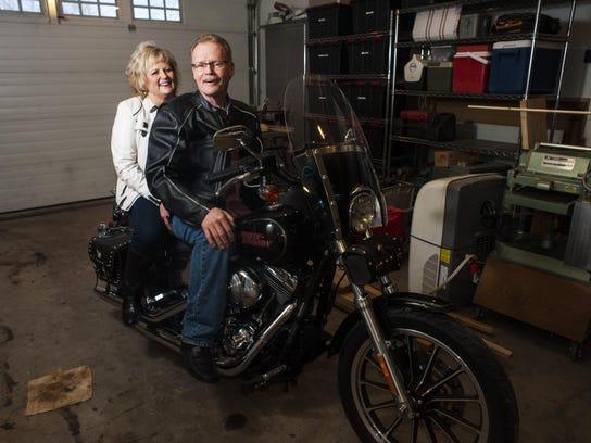 Sheryl and Chuck Hopkins sit on a Harley Davidson motorcycle
