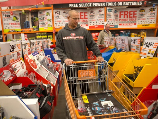 Larry Casaus compares prices Friday at the Home Depot in Farmington.