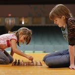 Jada Dusek, 7, left, and Abby Miller, 16, play a game of checkers using chess pieces during a Big Brothers Big Sisters of Great Falls Buddies program at West Elementary School in 2013.
