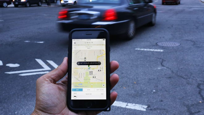 An UIber application is shown as cars drive by in Washington, D.C.