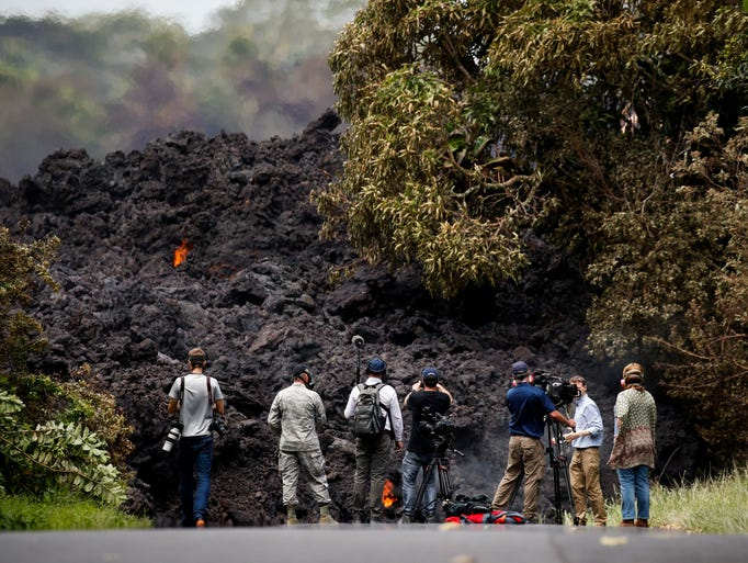 Members of the media record a wall of lava entering