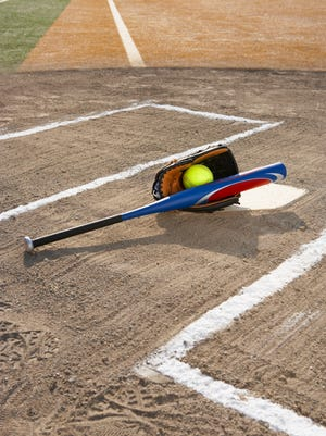 Softball, softball glove and bat at home plate