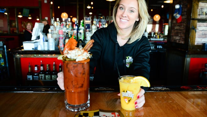 Crab Cake factory bartender Jackie Jenkins with their famous bloody mary and orange crush on Friday, Dec. 23, 2016.