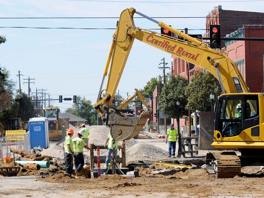Garney Construction workers lower a safety cage into the 10-foot deep trench at the intersection of Elm and First streets as they install a new sewer line in Downtown Henderson Tuesday afternoon in September 2010.