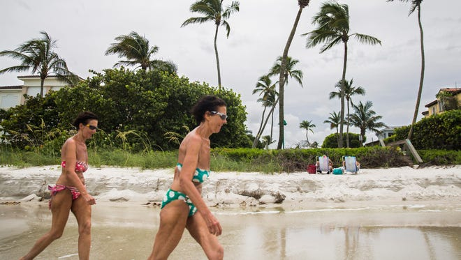 Hanna Bernhardt, left, and Erika Bernhardt walk along the beach as two women sit above the eroded shore along the Naples Beach between Sixth and Seventh Avenue North on Tuesday, May 28, 2018.