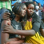 A survivor of an attack at Kenya's Garissa University College is comforted by a colleague.