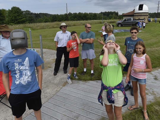 Keeping an eye on the progress of the  partial solar eclipse at the Ray and Ruthie Stonecipher Astronomy Center, Sturgeon Bay, on Monday, Aug. 21, 2017, are front from left, Jacob Hooker of Sturgeon Bay, and Berit and Annika Borgnes of Stevens Point. To see more photos, go to: www.doorcountyadvocate.com.