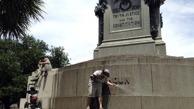 FILE - In this June 23, 2015, file photo, Joe Patrizzi III power-washes graffiti from a statue in Charleston, S.C., of John C. Calhoun, who was a vice president, U.S. senator and congressman from South Carolina.