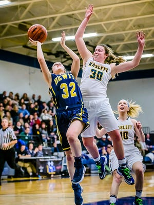 Sydnee Dennis ,30, of Haslett winds up to swat away a shot attempt by Jessah McManus ,32, of DeWitt.
