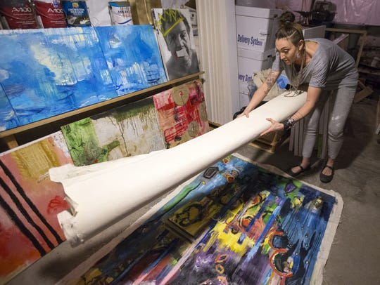 Cassie Kerns shows some of her art work in her basement
