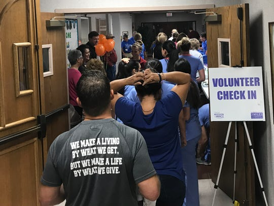 At 5:05 a.m., a steady stream of volunteers is filing