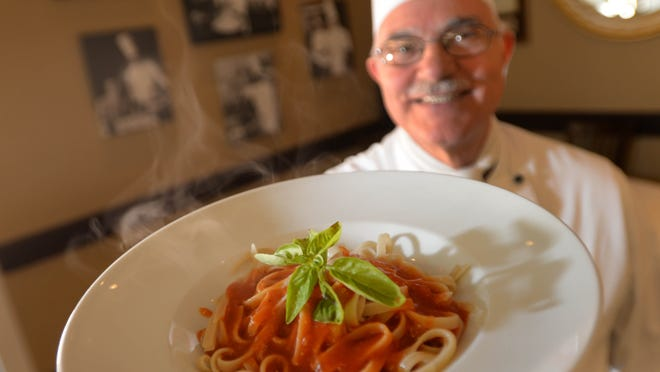 Giuseppe Brucia, owner and head chef at Ristorante Giuseppe, holds a plate of Fettucine with fresh tomato sauce.