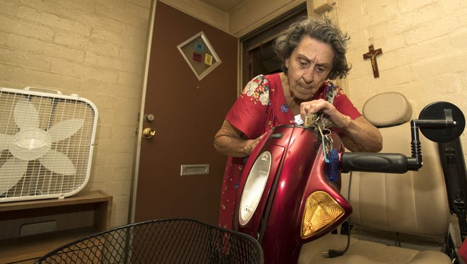 Yvonne Bridges, 88, checks to see if her scooter is charged so she can continue her Block Watch tour in a Phoenix public housing project.