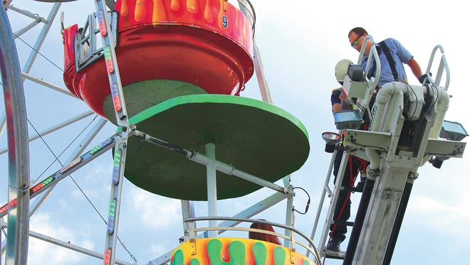 Members of the Greeneville Fire Department help people off the Ferris wheel at the Greene County Fair in Greeneville, Tenn.,  Aug. 8, 2016 after 3 people in one tub were thrown out..