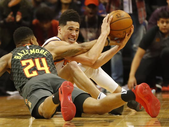 Suns guard Devin Booker grabs a loose ball from Hawks guard Kent Bazemore during the fourth quarter on Tuesday.