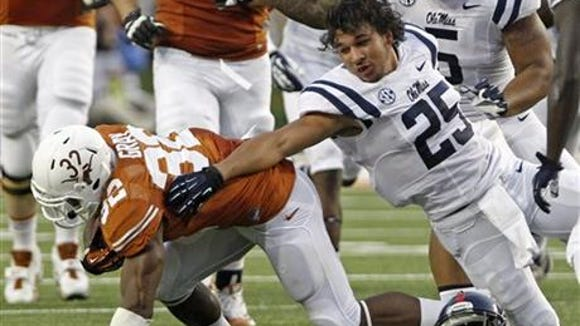 Ole Miss safety Cody Prewitt, right, makes a tackle during the Texas game while also losing his helmet.