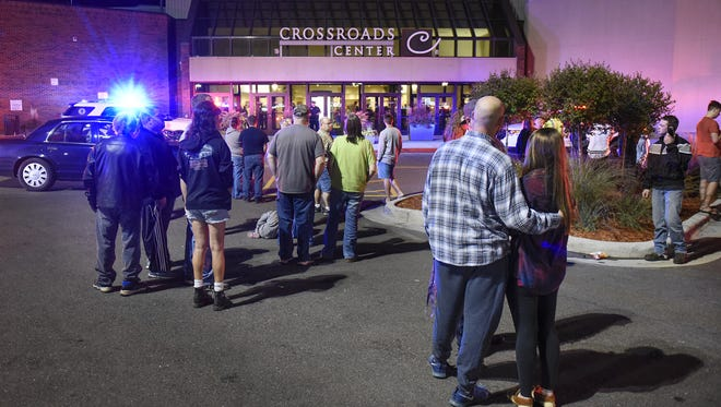 People stand near the entrance on the north side of Crossroads Center between Macy's and Target on Saturday, Sept. 17, 2016, as officials investigate a reported multiple stabbing incident.
