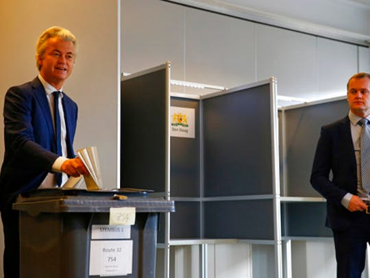 A security guard looks on as Geert Wilders, left, cast