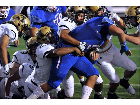 Cooper High School's Anthony Arellano is brought down by four Abilene High School Eagles during Friday's crosstown showdown Sept. 15, 2017. Cooper won, 49-35.