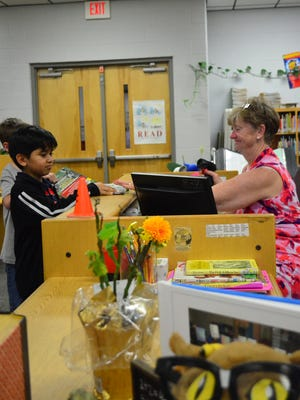Benny Bills librarian Linda Perkins checks out books for students.