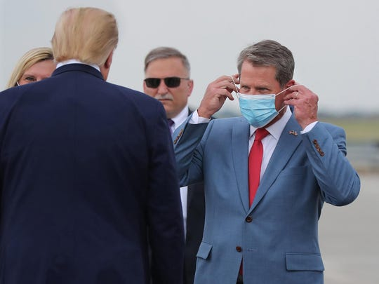 Georgia Gov. Brian Kemp, right, greets President Donald Trump as he visits Georgia to talk about an infrastructure overhaul at the UPS Hapeville hub at Hartsfield-Jackson International Airport in Atlanta on July 15.