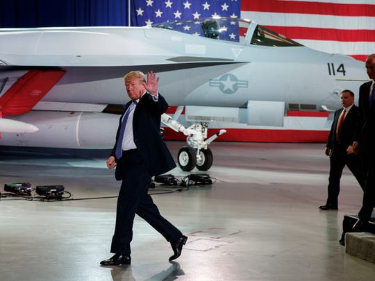 President Donald Trump waves as he walks off after participating in a roundtable discussion on tax policy at the Boeing Company, Wednesday, March 14, 2018, in St. Louis.